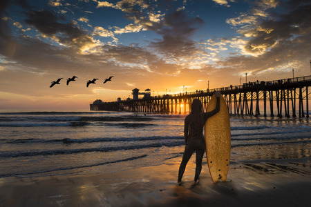 Surfer near the Oceanside Pier. Oceanside is 40 miles North of San Diego, California.