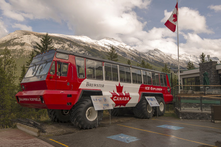 One of the Columbia Icefield vehicles parked in front of the Banff Gondola base building. Editorial
