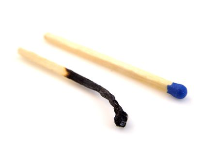 whote: burnt matchstick next to blue headed matchstick isolated on whote background