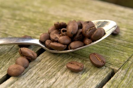 Arabica coffee beans on a silver teaspoon with wood in the background Stock Photo - 1063594