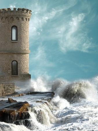 castillo medieval: La torre medieval con agitación costa y grandes rocas Foto de archivo