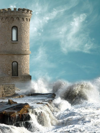 Medieval tower with agitated coast and big rocks photo