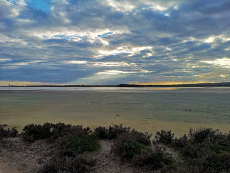 A dramatic sunset over Salt Lake in Larnaca, Cyprus. The lake is during drought season in December and there is almost no water in it. The surface is muddy and wet.