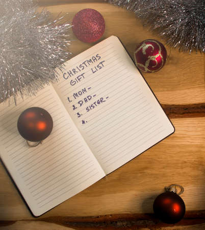 "Christmas gift list for a family and dark red baubles with festive ornaments on a retro wooden table. An English text handwritten in a paper notebook ""Christmas gift list - mom, dad, sister""."