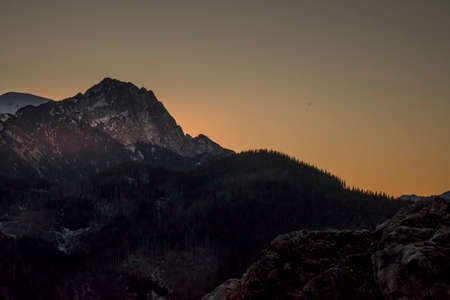 The sun is setting behind Giewont Peak - a legendary peak in Tatra Mountains, Poland. Selective focus on the rocky ridge, blurred background.