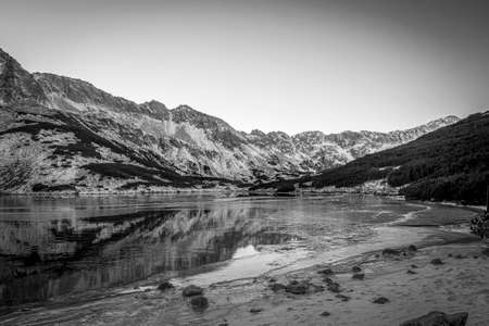 Black and white view of Dolina Pięciu Stawów Polskich, Tatra Mountains, Poland. A valley with a lake which is starting to freeze. Selective focus on the rocks, blurred background.