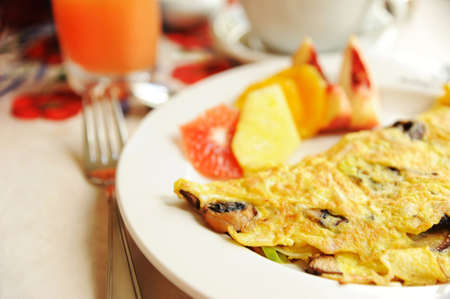 Omelet served with fruits and grapefruit juice