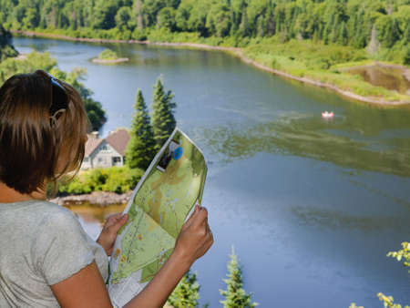 Female tourist holding a map of Jacques Cartier Park trails in Quebec, Canada