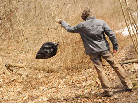 Suspicious man throwing out the garbage bag into the forest
