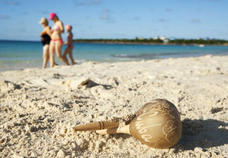 Wooden rattle on Cuban beach with tourists in the background