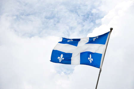 Flag of Quebec with white cross and emblem with the clouds in the background Stock Photo
