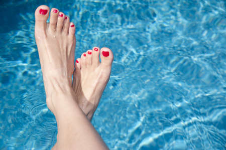 Attractive females feet extended above the swimming pool