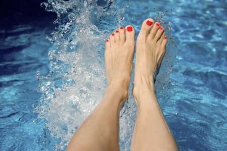 Attractive females feet splashing in the swimming pool water Stock Photo