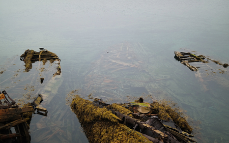 sunken boat: A sunken wooden boat with algae and moss. Stock Photo