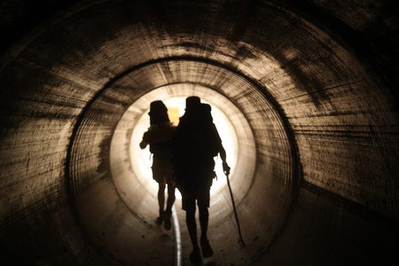 two visions: Two persons walk to the light in the end of the tunnel. Stock Photo
