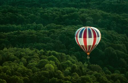 Flying hot air ballon below the forest, captured in mid summer while flying another hot air balloon. Stockfoto