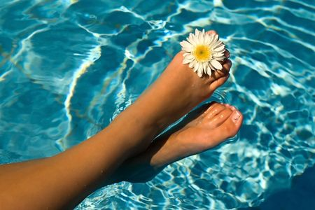 Womens feet in the water pool flowers. photo
