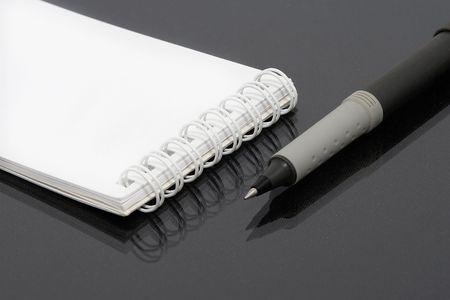 White notebook pen, black background. photo