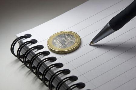 pad pen: Panel de escritura, l�piz y un euro.  Foto de archivo