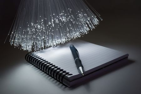 optical fiber: Notepad and pen and optical fiber floodlight. Stock Photo