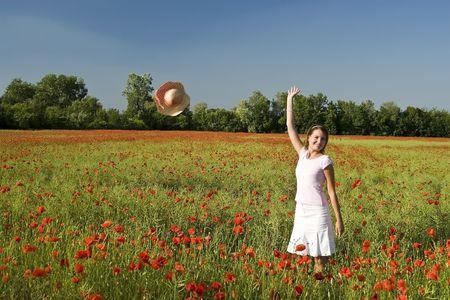 A beautiful woman feels happy on the poppy field. Stock Photo - 5306478