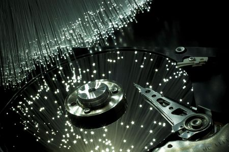 optical fiber: Computer hard disc, illuminated optical fiber.  Stock Photo