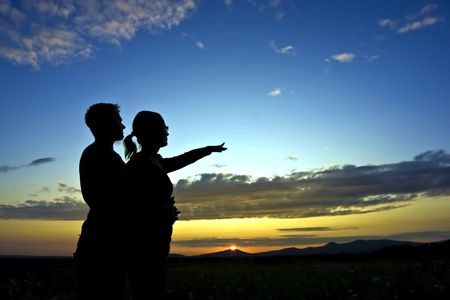 Boy and girl looking at the beautiful sunset. photo