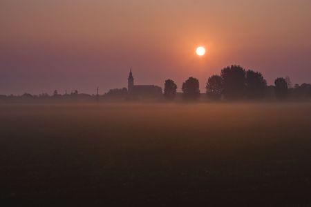 Sunrise over the foggy city photo