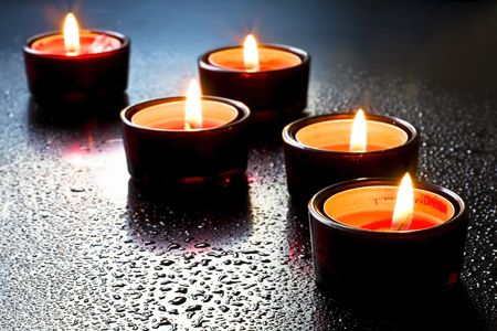 Red candles in the dark background of water drops. Stock Photo - 6062259