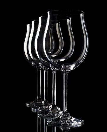 Four glasses of wine, primarily located in a dark background.  photo