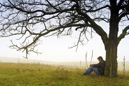 hombre solitario: Hombre descansando bajo un �rbol. Foto de archivo
