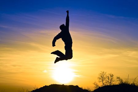 succes: Young athletic man jumps in the sunset.