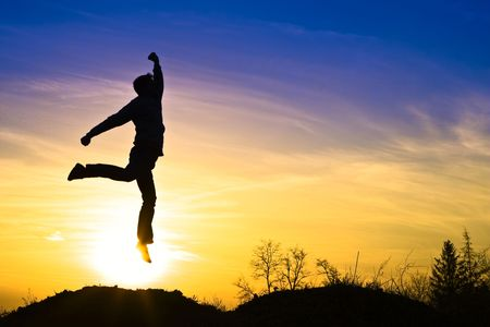 Man in the sunset, happy and jumps. photo