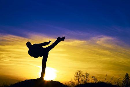 patada: Hombre karate en la puesta de sol.