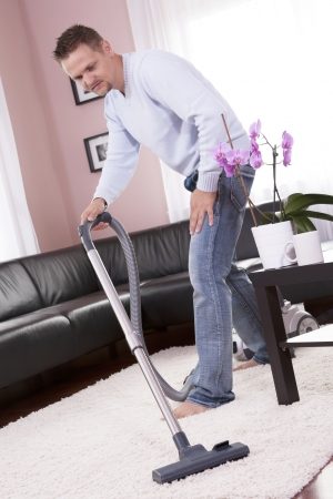 Man in the modern living room, vacuum cleaning.