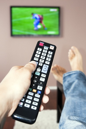 viendo television: Joven mirando la televisión, el control remoto en la mano.