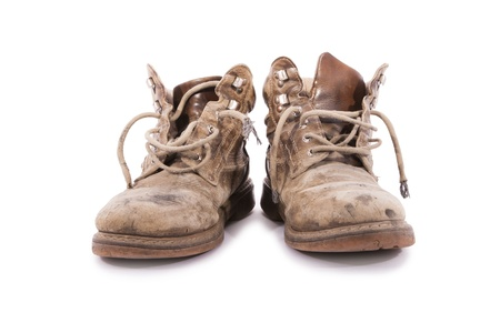 muddy clothes: A pair of dirty brown boots.