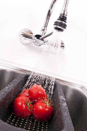 Kitchen faucet in tomatoes washed down. Stock Photo