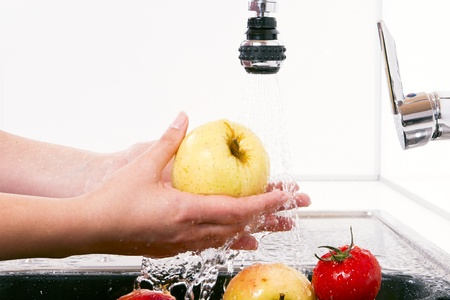 Women wash the apples in the kitchen.