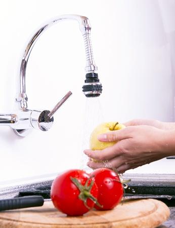 hygi�ne alimentaire: Les pommes m�res sont lav�es dans la cuisine.