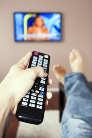 television remote: Men with the remote control, front of the television. Stock Photo