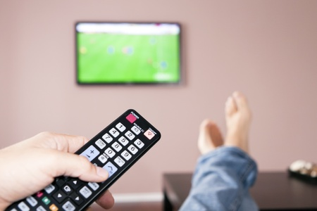 Men with the remote control, front of the television. Stock Photo