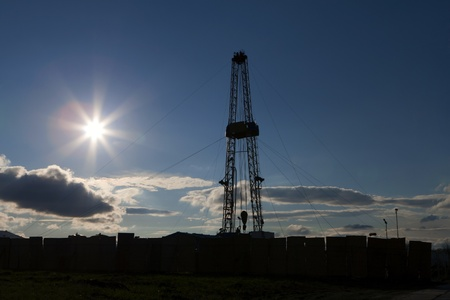 Oil rig in bright sunlight blue sky