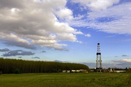 Oil rig, cloudy sky in the field