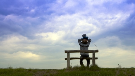 The man sits on a bench under a cloudy sky