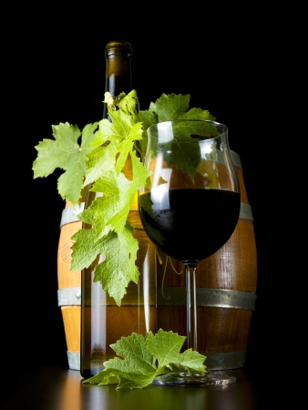 Barrels of wine bottles and glasses, decorated with vine leaves  photo