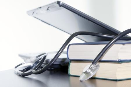 medico computer: Stetoscopio medico e laptop e libri