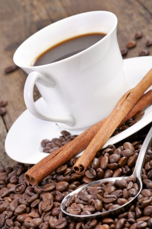 Coffee cup surrounded by coffee beans and scoop  photo