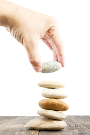 His hand stacking the stones  Standard-Bild