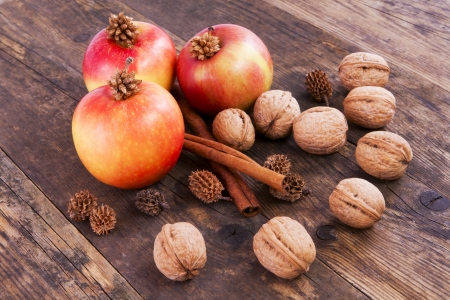 Apples, nuts and cinnamon on wooden board. photo